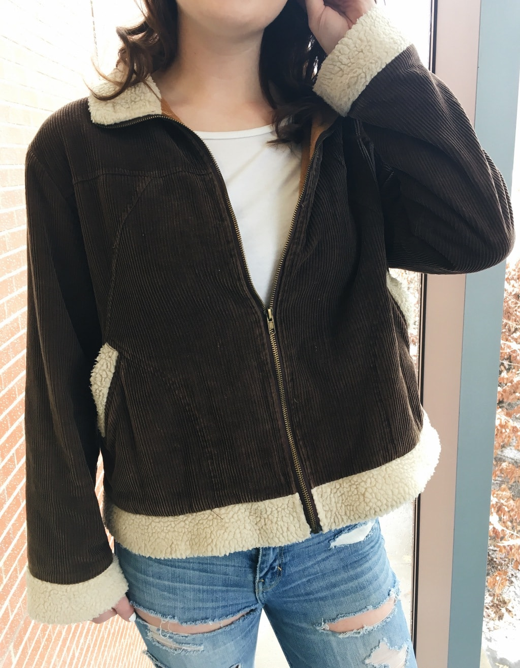 Erin's corduroy zip-up jacket has cream shearling details and a white tee underneath.