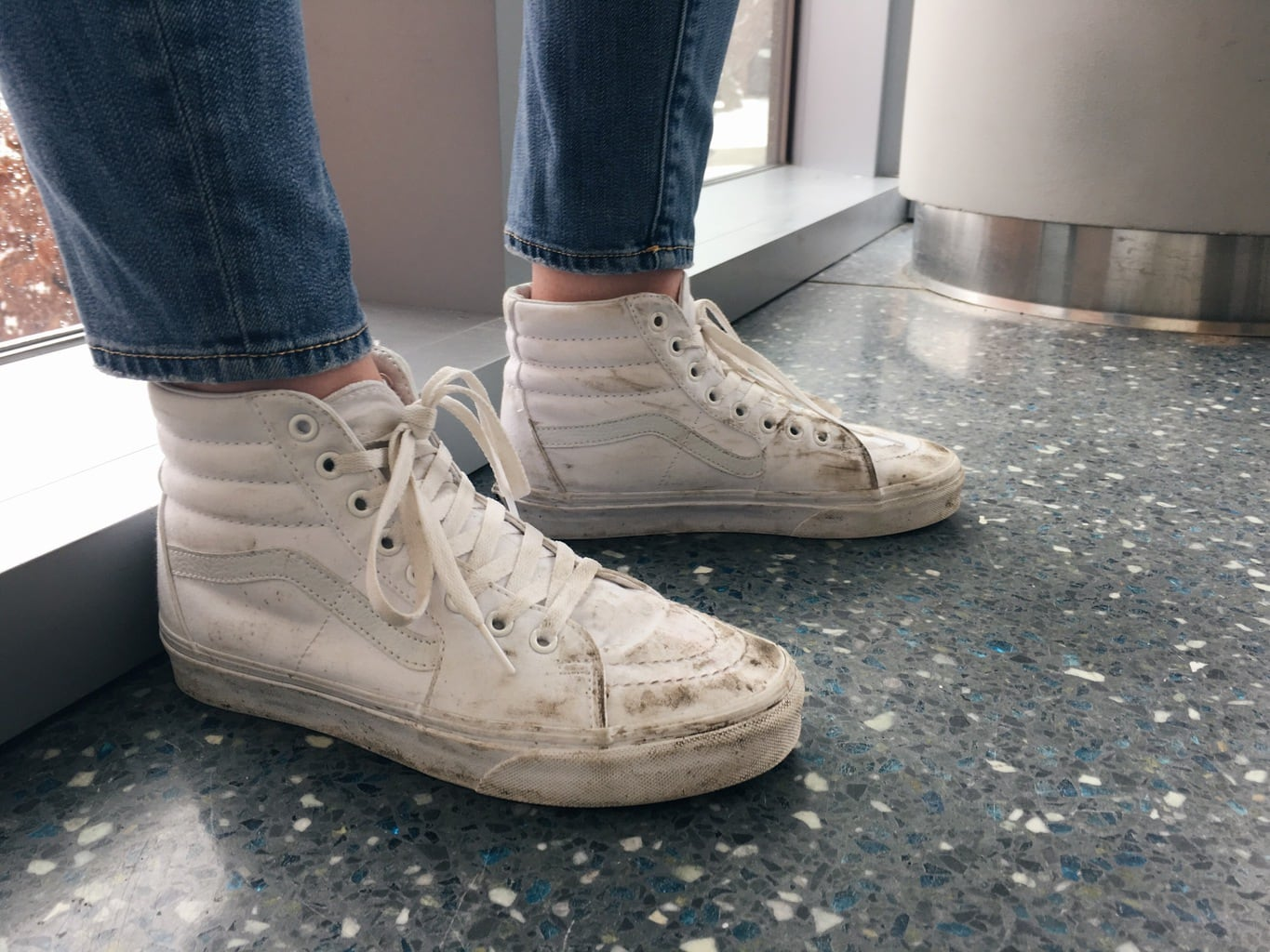 These high-top all white Vans lace-up sneakers are worn-in from walking across campus.