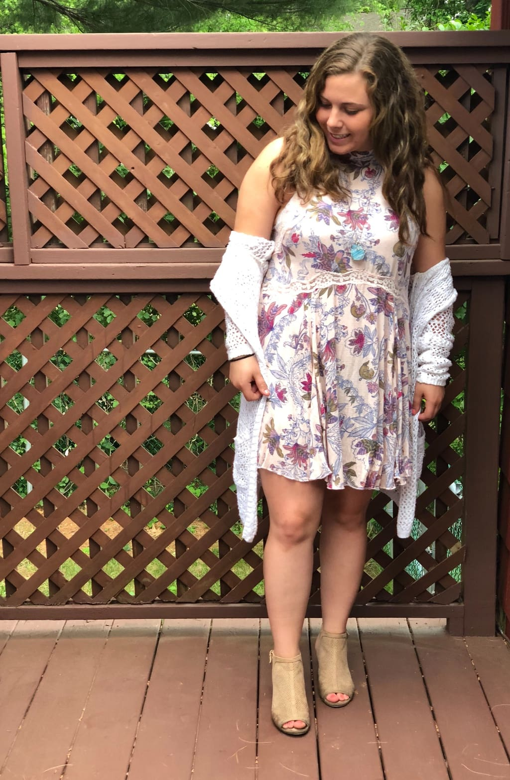 UMass Amherst Student Hannah wears a simple floral high-neck cream dress with a lace empire waist, a white open knit cardigan, and taupe peep-toe heeled booties.