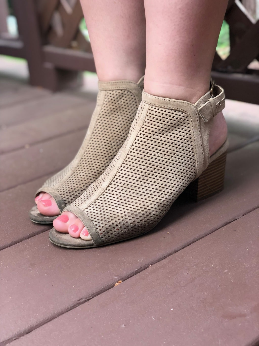 Hannah's taupe peep-toe heeled booties are chunky-heeled and have ankle straps.