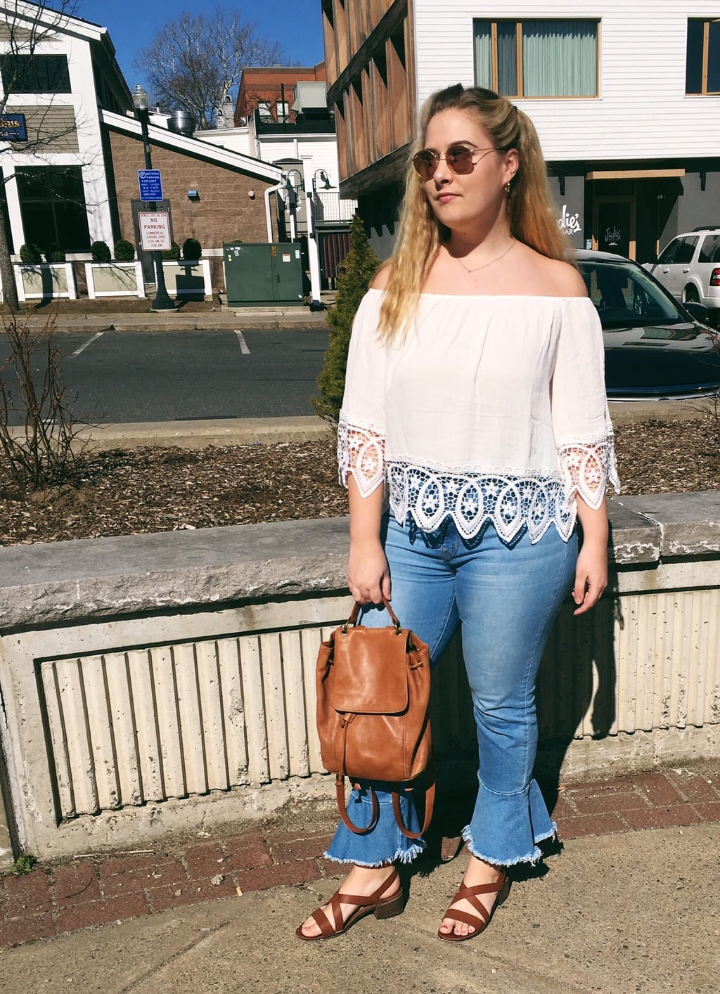 University of Massachusetts Amherst student Kendall wears a cream off-the-shoulder bohemian top with lace detailing on the sleeves and hem with high-waisted light-wash denim cropped flare jeans, a leather bucket backpack, and brown leather strappy sandals with chunky heels.