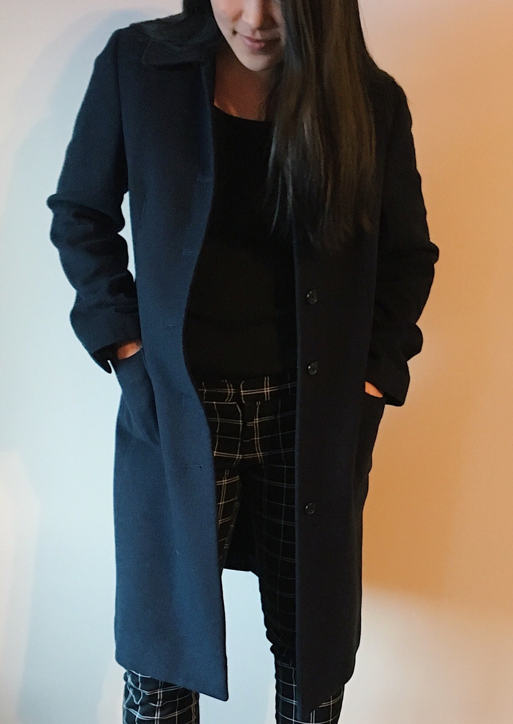 Yan Ni sports a long line navy peacoat with a black sweater top and black and white plaid pants.
