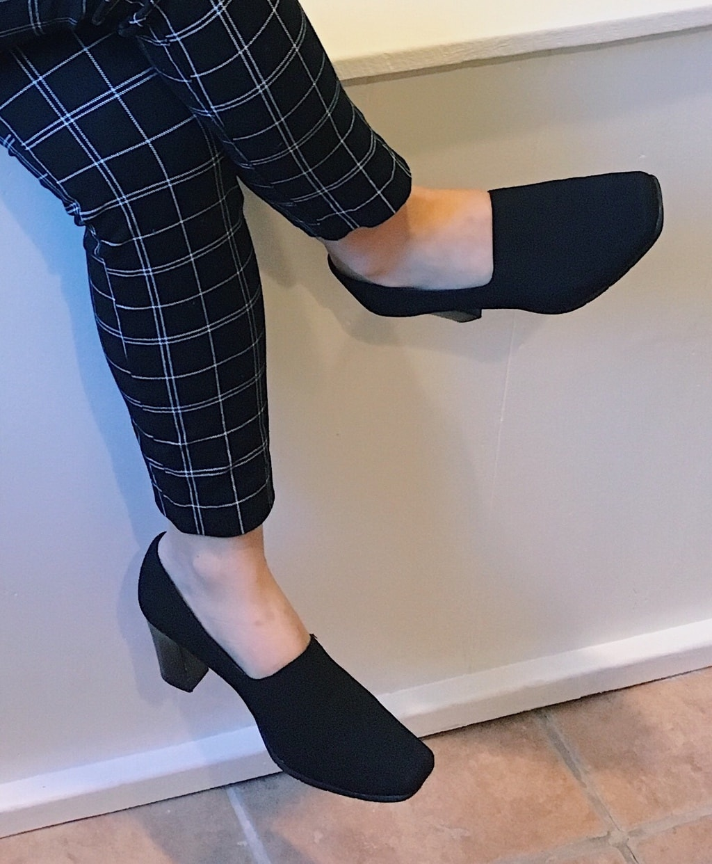 Yan Ni wears a pair of chunky-heeled black pumps that cover most of the top of her foot for comfort and modesty.