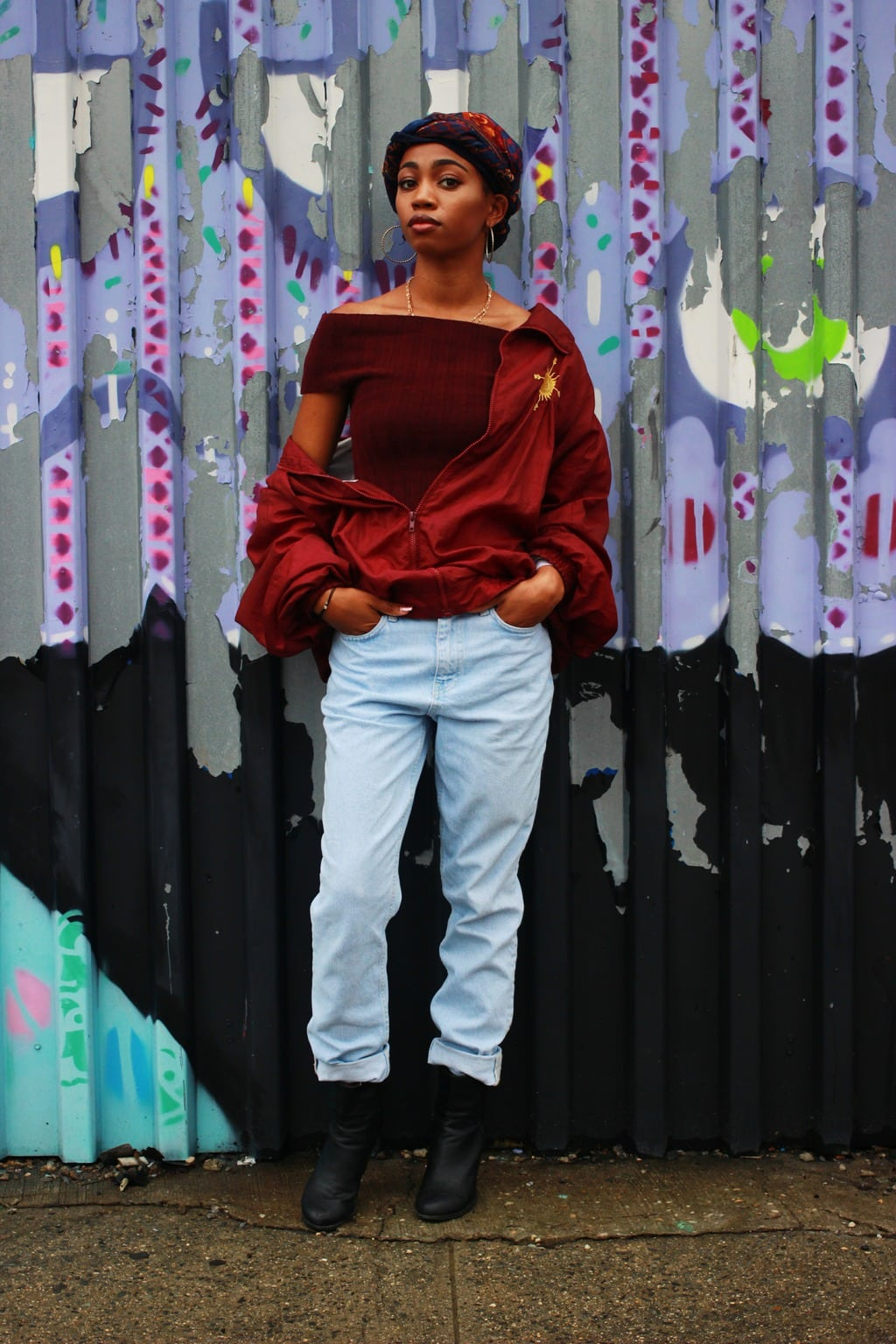 Student style; oxblood off-the-shoulder top, vintage windbreaker jacket, headscarf, distressed light-wash jeans, and chunky black booties.