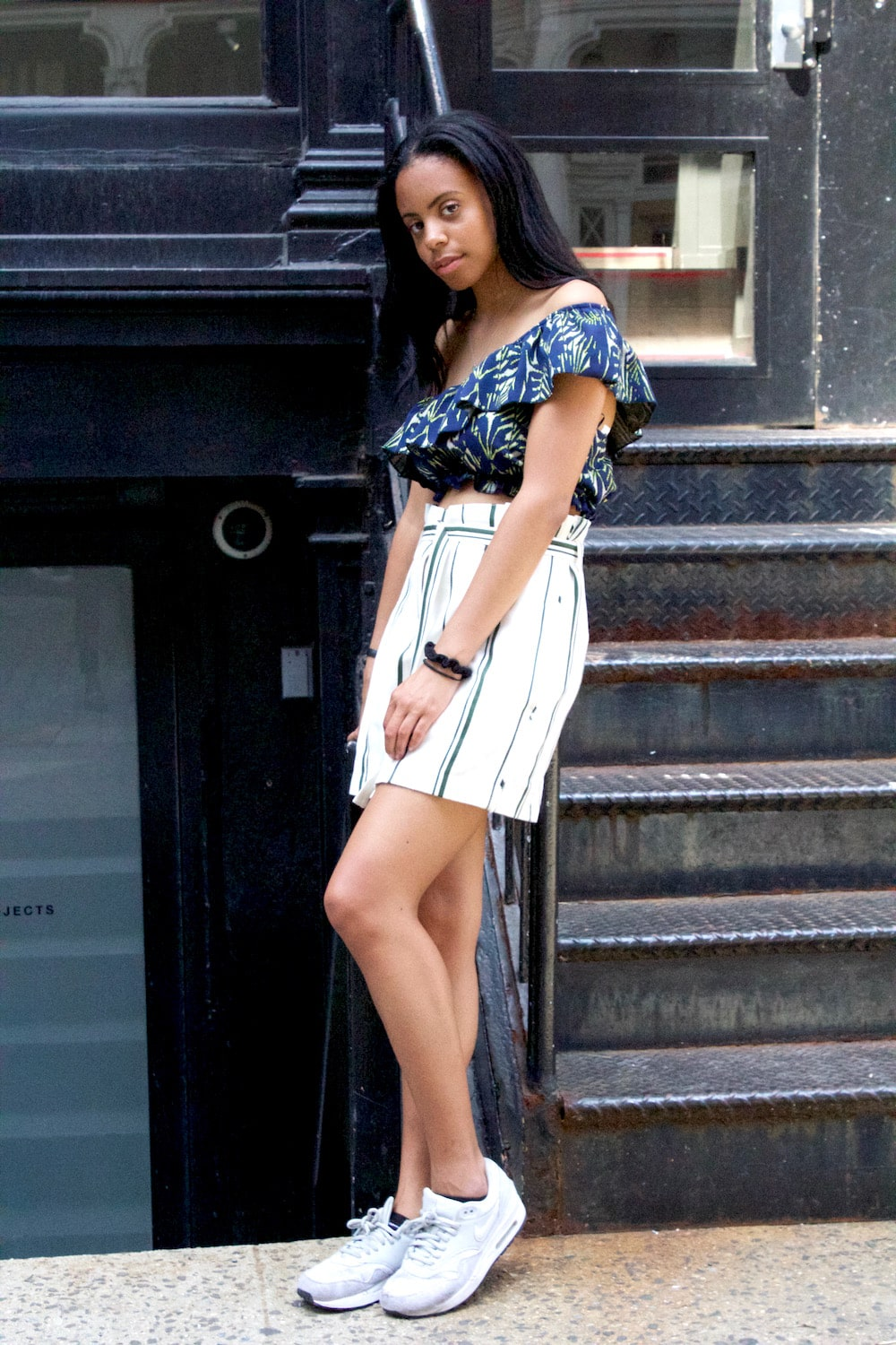 College style in NYC: Notre Dame student Sierra wears a vertical striped mini skirt, off-the-shoulder palm print crop top in navy and green, and gray Nike sneakers
