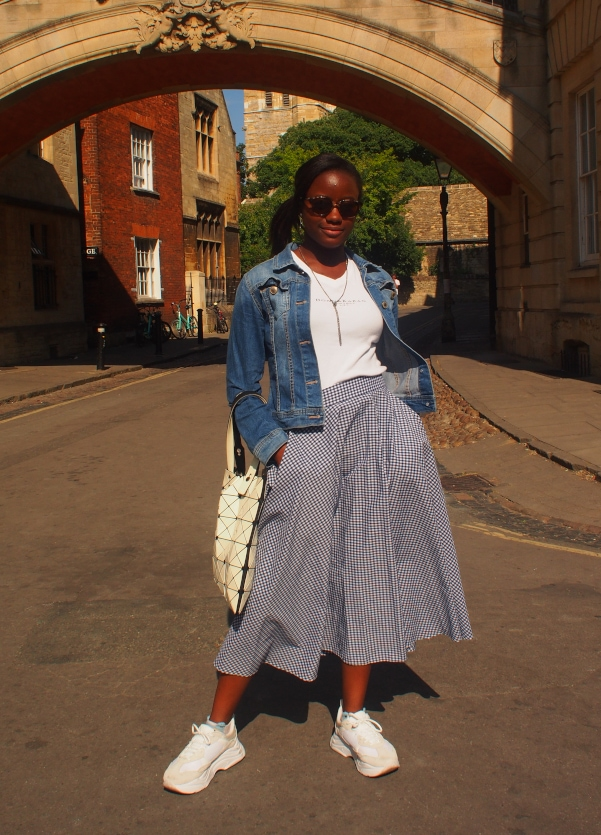 University of Oxford student Chelsea wears a vintage white v-neck tee with a blue and white plaid midi skirt, denim jacket, and white chunky sneakers.