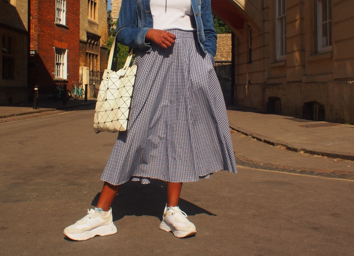 Chelsea wears a blue and white gingham midi circle skirt with chunky oversized white sneakers.