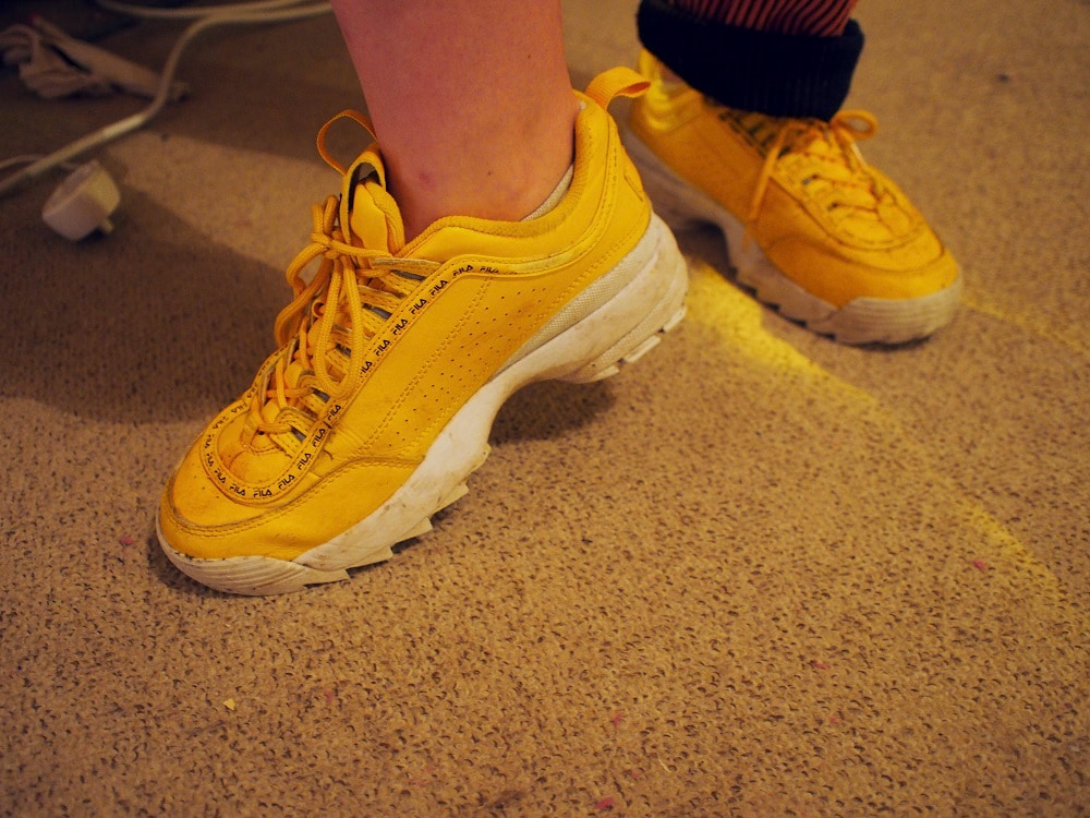 Martha wears chunky yellow sneakers with white soles and yellow laces.