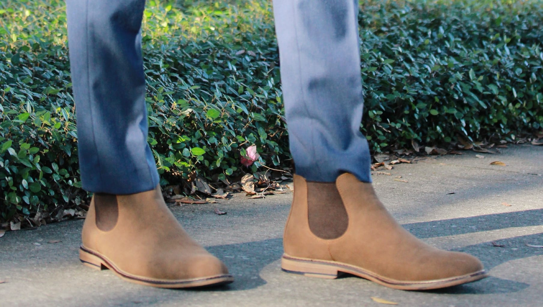 Flat tan brown Chelsea boots with slim fit blue slacks.