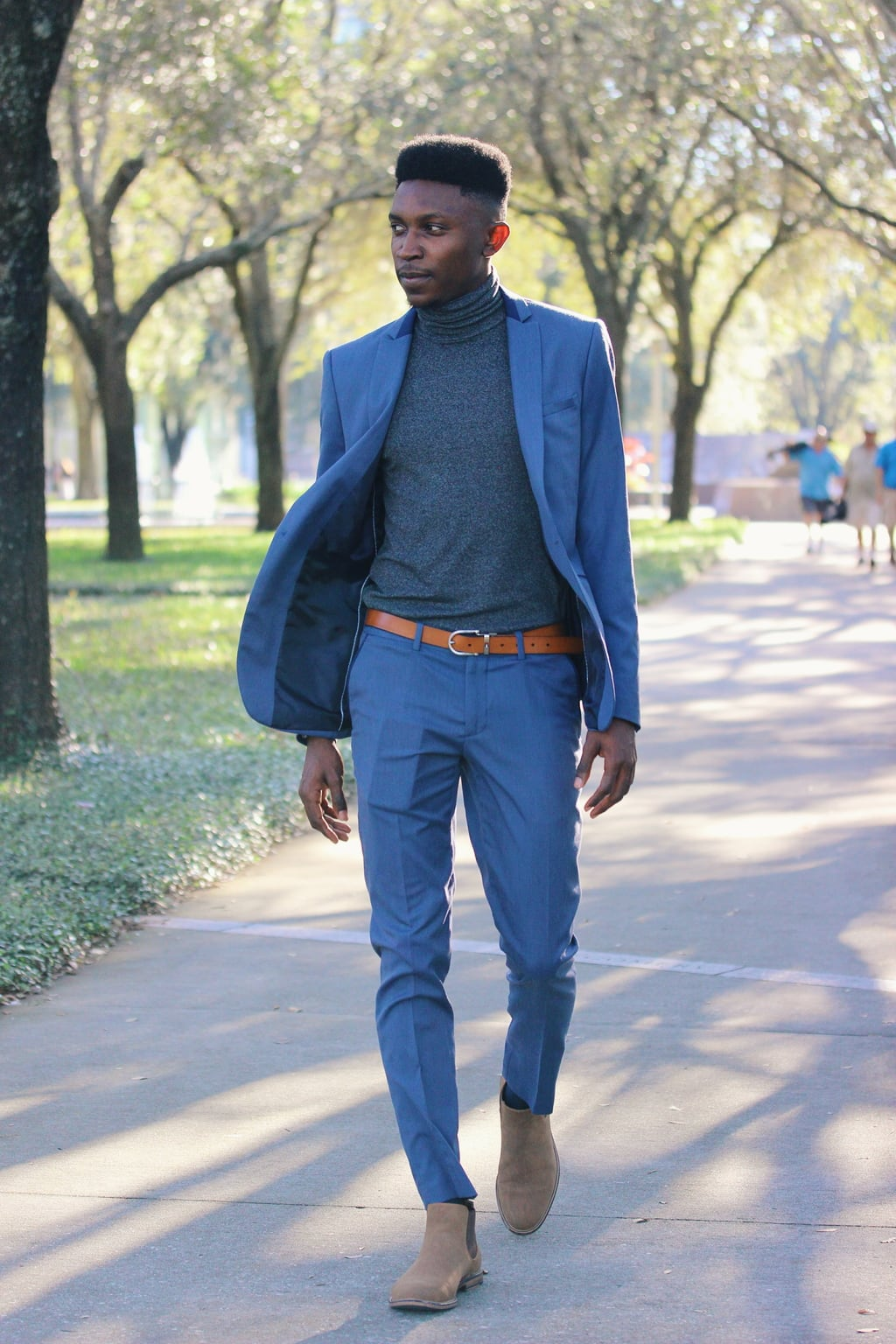 Dressed up for class, Adedamola wears a two-piece navy blue slim fit Zara suit with a heather grey turtleneck, ankle boots, and skinny brown belt.