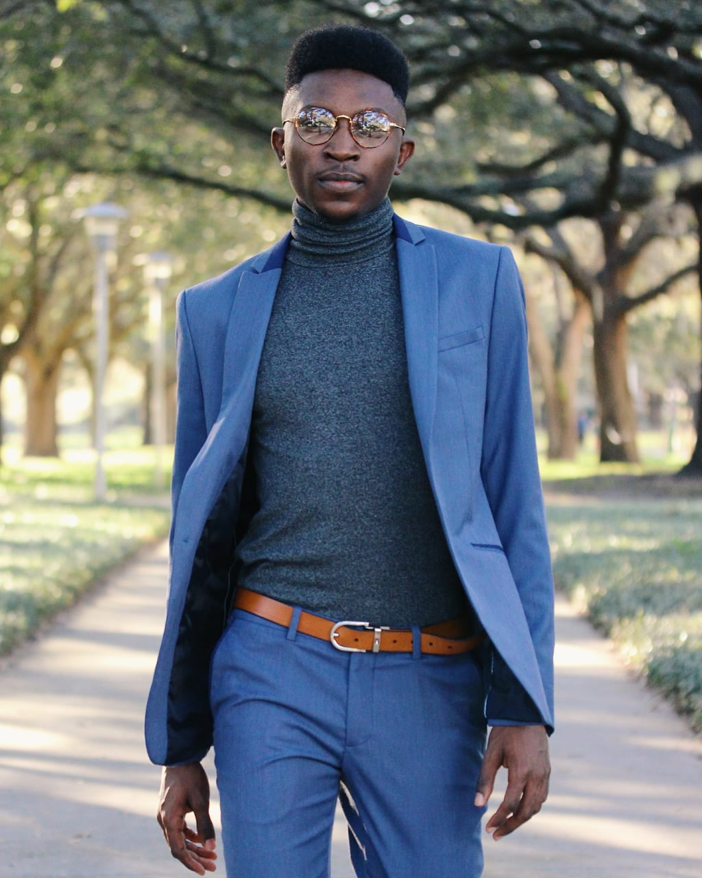University of South Florida student Adedamola wears a slim fit blue Zara two-piece suit with a heather grey turtleneck and round tortiseshell glasses.