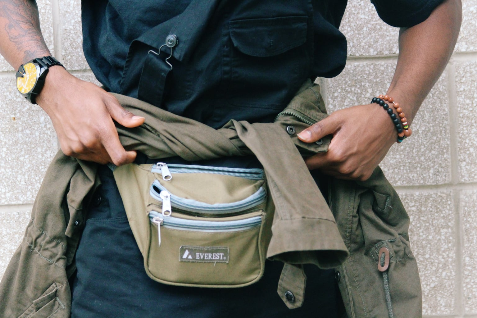 Karon wears a light brown fanny pack with grey zippers and an olive anorak jacket. He accessorizes with black and orange beaded bracelets.
