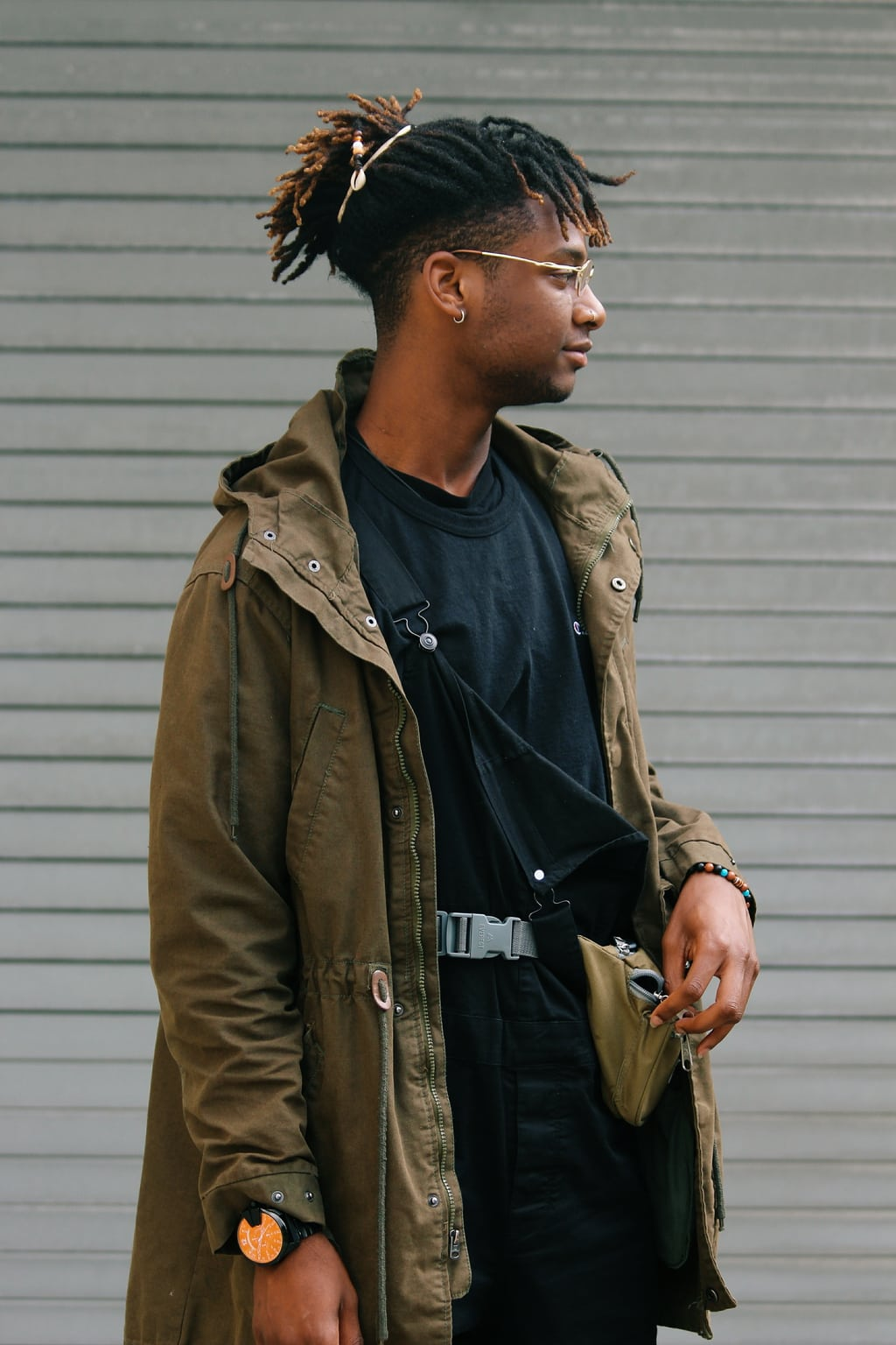 Karon sports black overalls and a black tee with an olive anorak jacket.