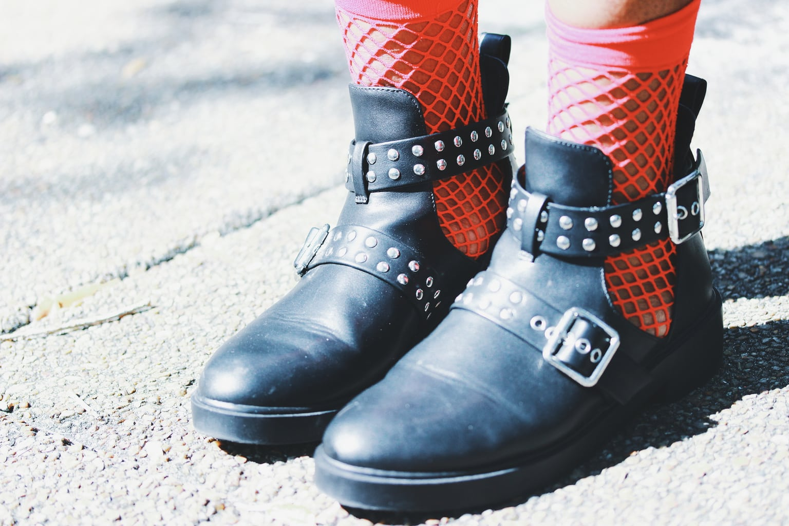 This student's look is polished off with flat studded sandal-boots with multiple buckles and red fishnet socks.