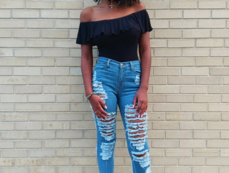 Payton, a University of South Florida student, rocks an 80-inspired look. Her off-the-shoulder black ruffled bodysuit tucks into her ultra shredded light-wash denim jeans. She polishes off her look with a cross choker necklace and ultra reflective round sunglasses.