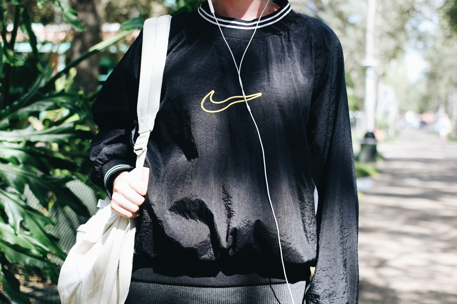 Taylor wears a vintage Nike oversized windbreaker pullover top.