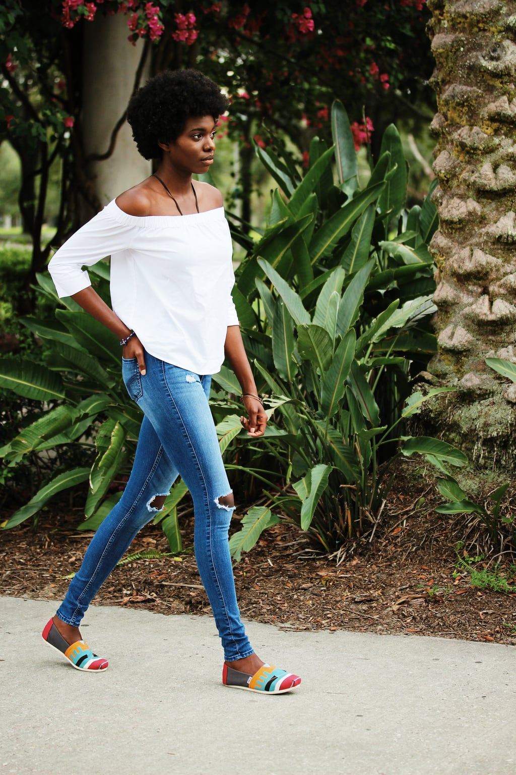University of South Florida student Uchoku wears a simple white off-the-shoulder blouse with distressed light-wash jeans and colorful Toms shoes.