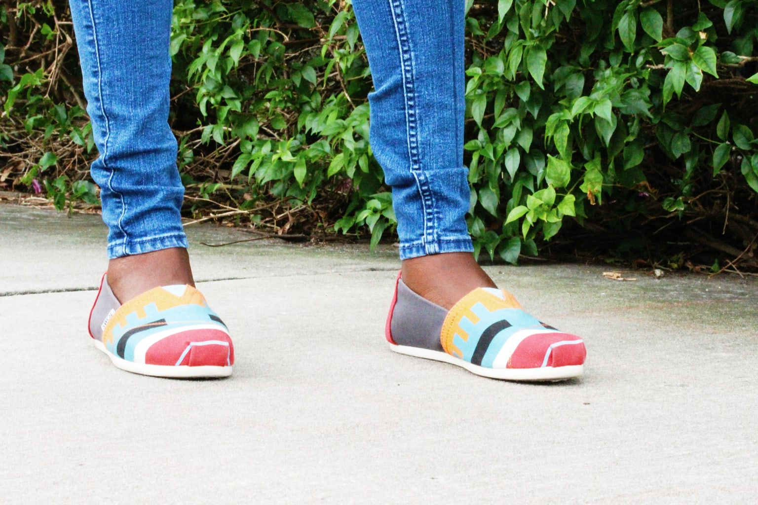 Uchoku wears bright blue, yellow, white, gray, and red Toms sneakers with straight-leg denim jeans.
