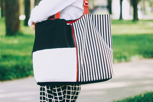 Black and white colorblocked tote bag with stripe accents and red straps.