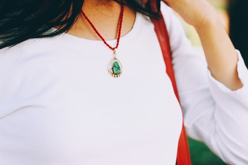 Pops of red: an heirloom jade stone pendant necklace encompassed by gold and a bright red chain.