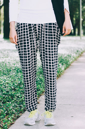 Black and white comfortable and loosely-fitted windowpane print trousers, paired with simple sneakers and neon green shoelaces.