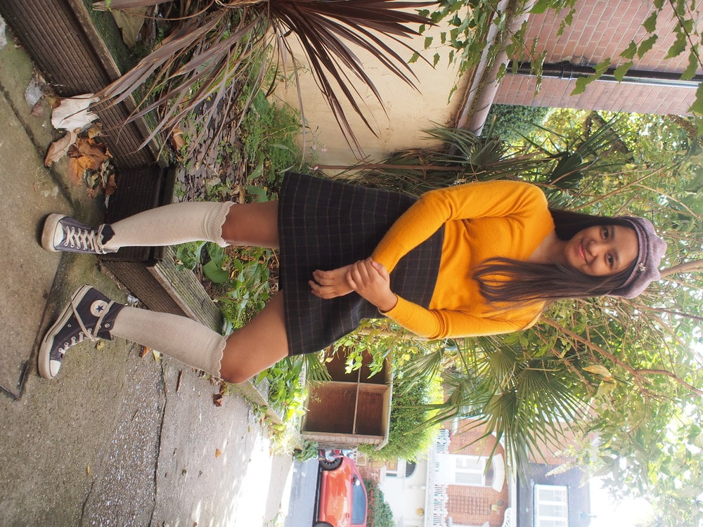 University of Westminster student Sharen wears a mustard yellow-orange long-sleeve v-neck sweater with a high-waisted plaid a-line schoolgirl skirt, a purple hat, and ruffled knee-high socks with low-top Converse sneakers.