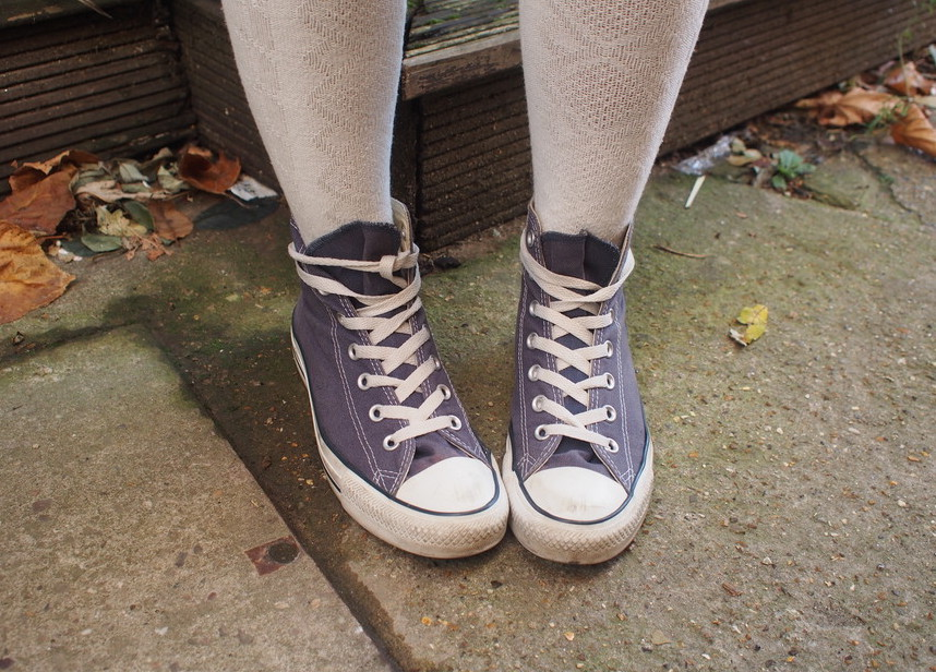 Sharen wears patterned white knee-high socks with low-top lilac Converse sneakers.