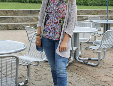 West Virginia University student Alyssa wears a blue, pink, and green loose floral blouse with an open-weave grey knit cardigan, mismatched jewelry, casual denim jeans, and loafer-style sandals.