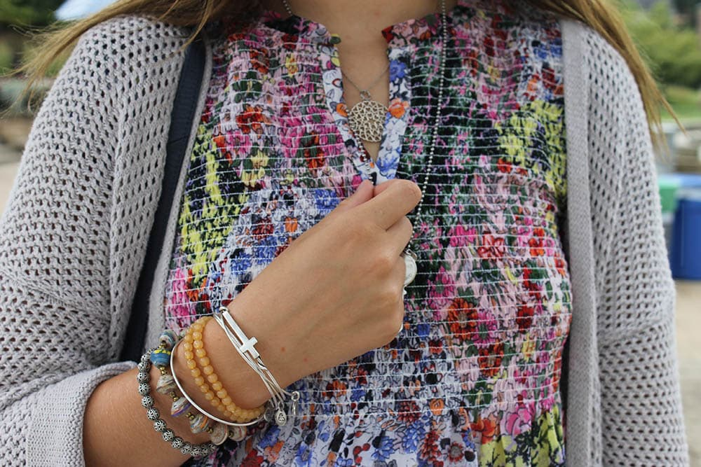 Alyssa wears mismatched jewelry including beaded bracelets and silver chain necklaces with pendants.