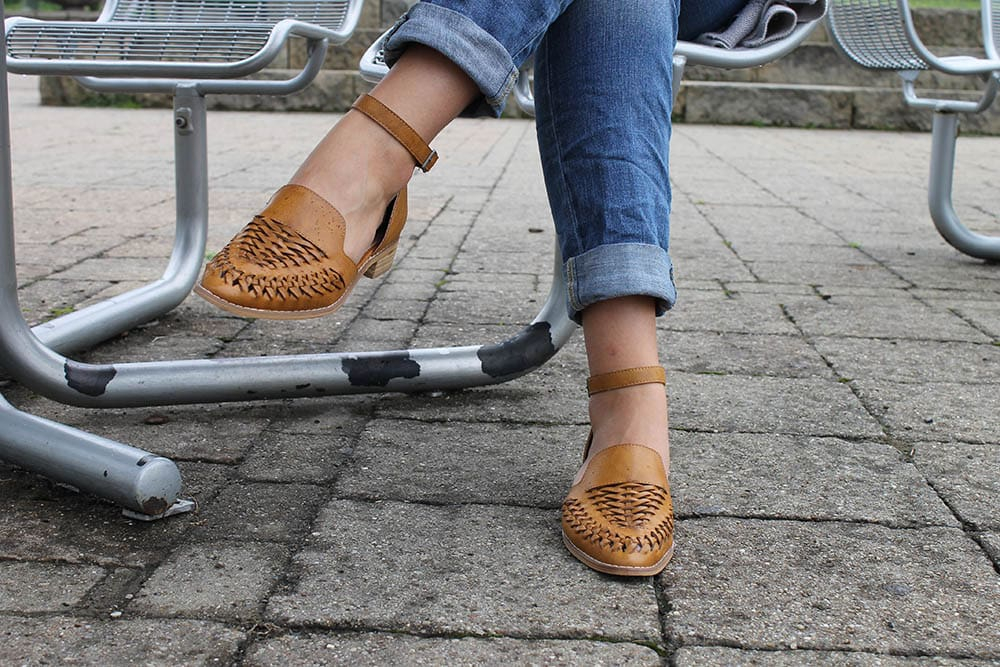 Alyssa's shoes are flat medium brown loafer-style sandals with ankle straps.