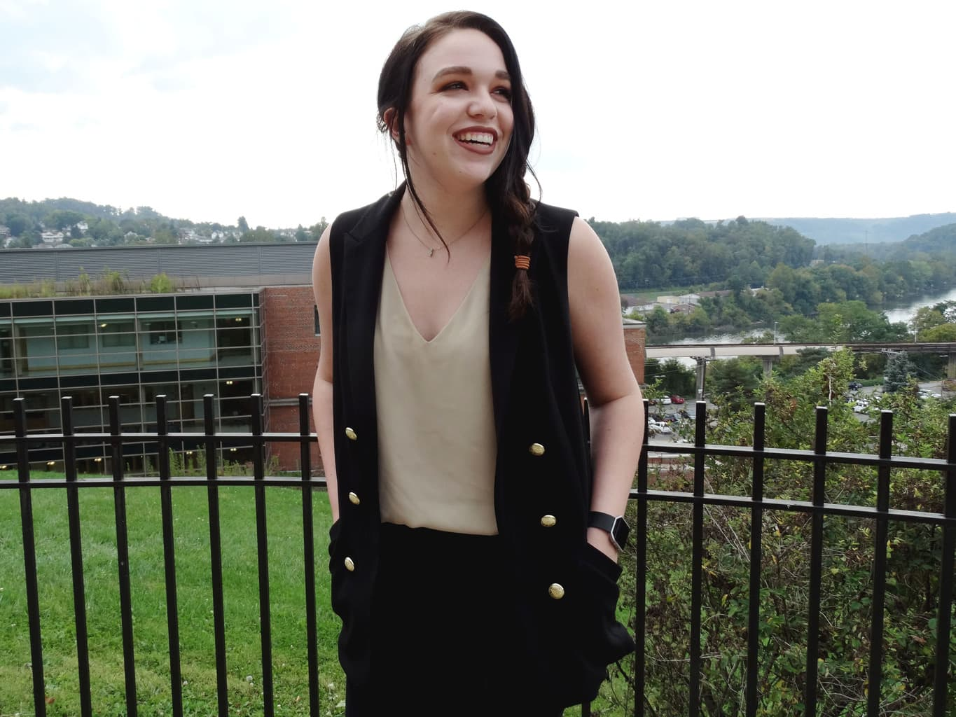 Bree wears a black military-style sleeveless vest with gold buttons and a tan tank top tucked into black trousers.