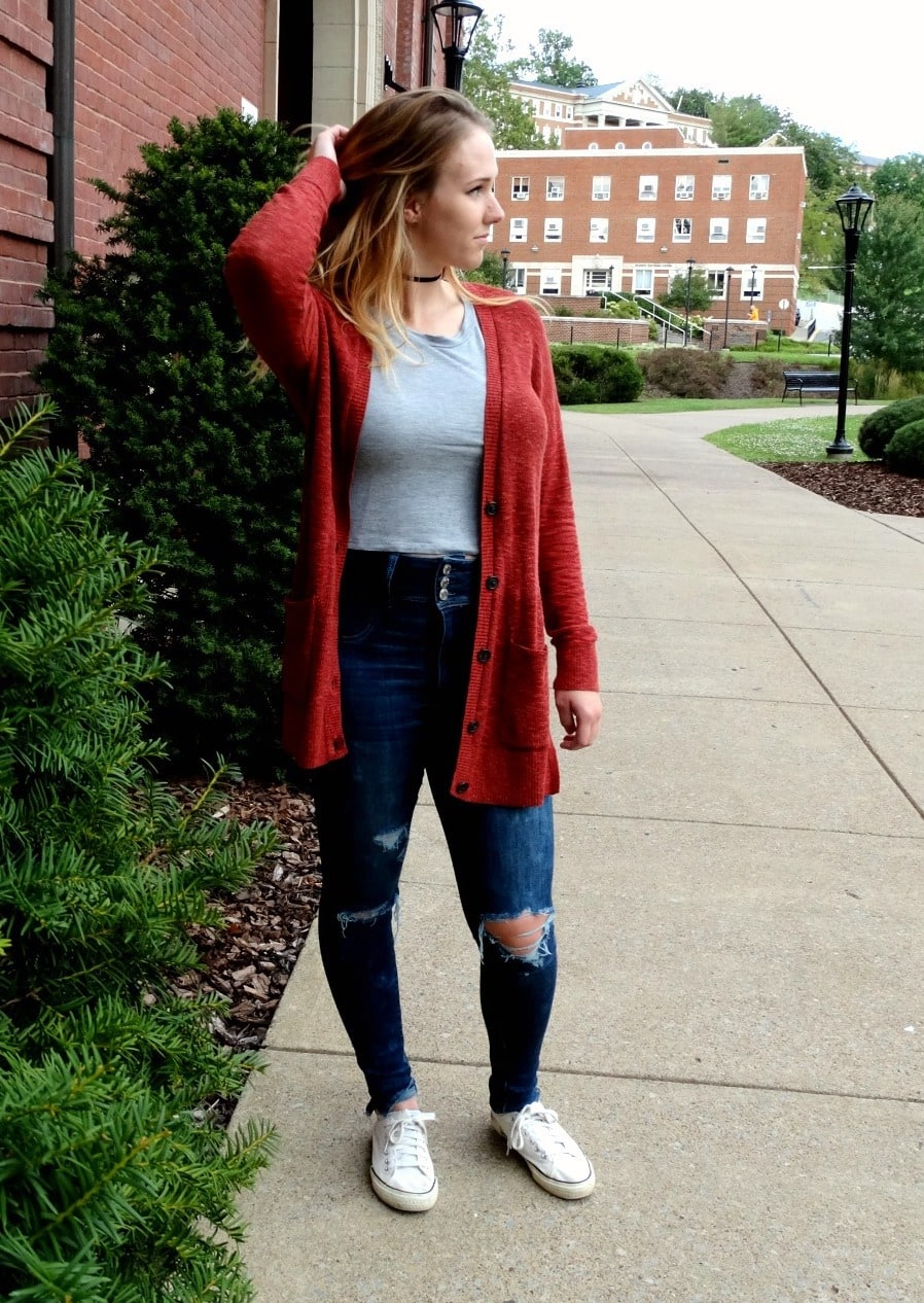 West Virginia University student stands out in a long red unbuttoned cardigan with a simple grey tee, distressed high-waisted dark denim jeans, Converse sneakers, and a black choker.