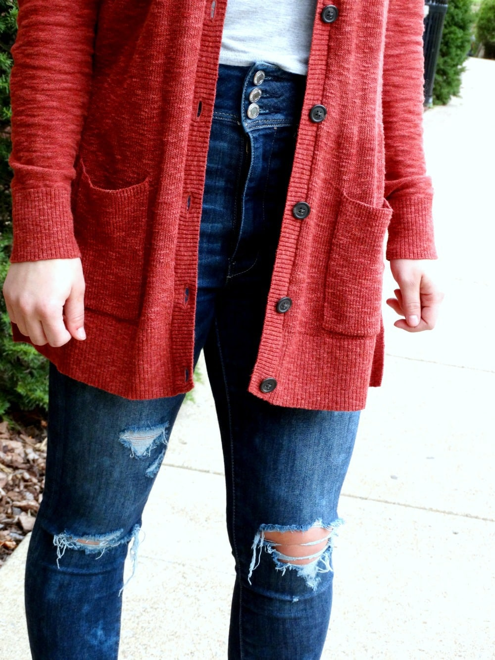 Long apple red cardigan with pockets contrasts against this West Virginia student's three-button denim jeans and basic grey t-shirt.