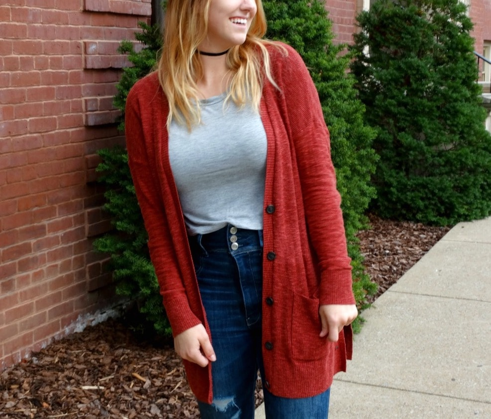 A cherry red long cardigan paired with high-waisted denim jeans and a light grey crew neck tee for fall.