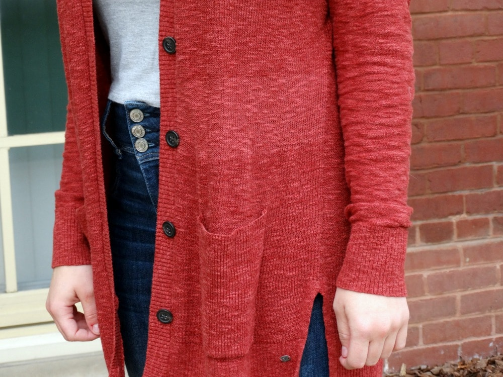 This bold red cardigan stands out against this student's grey tee and distressed denim jeans.