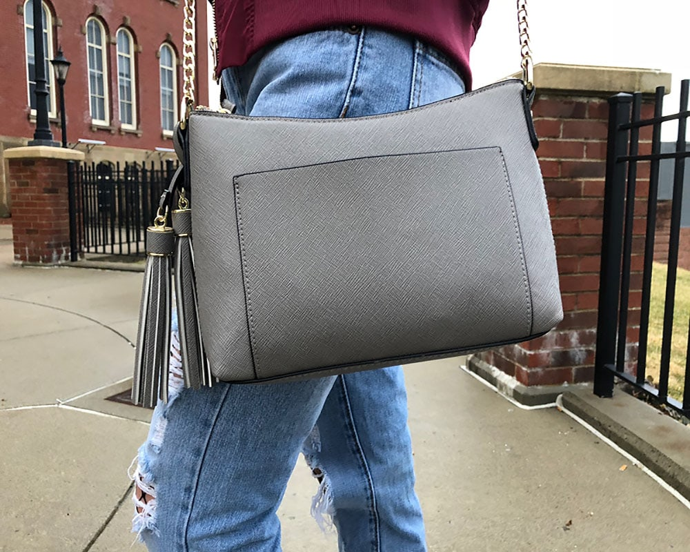 Courtni totes around a simple, crossbody grey purse with a gold chain strap and tassels.