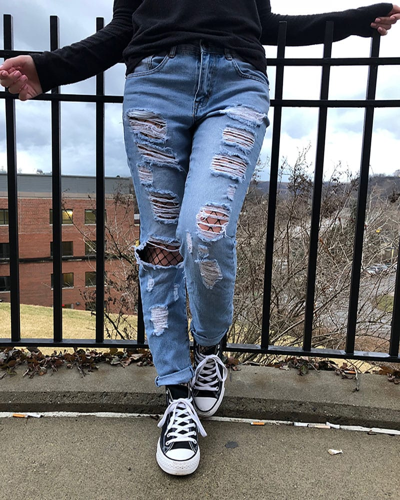 Courtni is punk in her shredded, light-wash denim jeans with black fishnets underneath and classic black Converse sneakers.