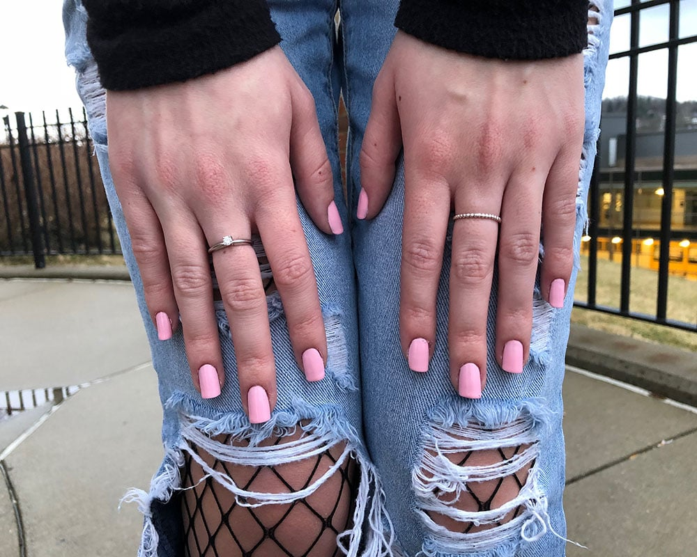 Courtni shows off her dainty silver rings with pastel pink glossy fingernail polish.