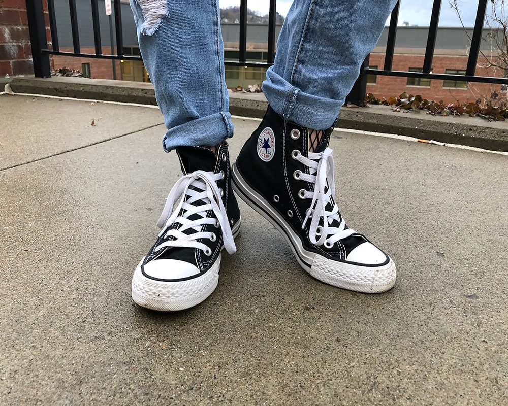 Courtni sports classic black Converse Chuck Taylors with her denim jeans rolled up to show off her fishnet tights.