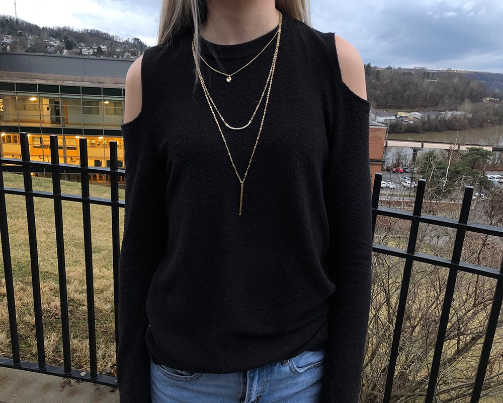 This black long-sleeve cold shoulder sweater is paired with a dainty gold layered necklace.