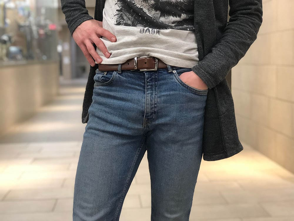 Davey wears medium-wash fitted denim jeans with a brown belt with a silver buckle.