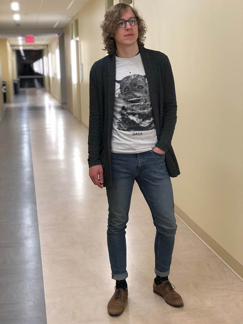 West Virginia University student Davey sports a light grey graphic tee with a dark grey knit cardigan with pockets, fitted and cuffed jeans, black dress socks, and flat brown lace up loafers.