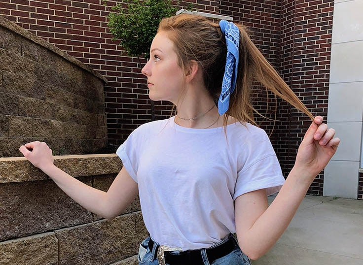 This West Virginia University student wears a traditional blue bandana tied around her ponytail with her white tee shirt.