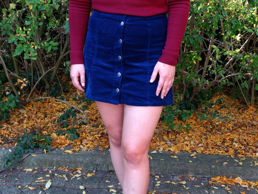 This blue high-waisted corduroy skirt buttons up the front.
