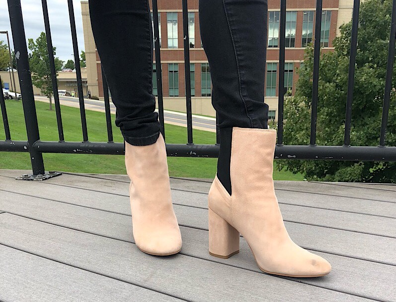 Gabriella wears black skinny jeans with tan heeled booties with black back panels.