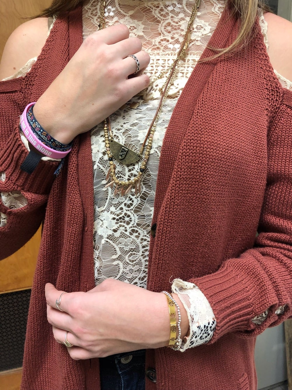 Gentry wears layers of bronze and gold beaded necklaces and mismatched bracelets.
