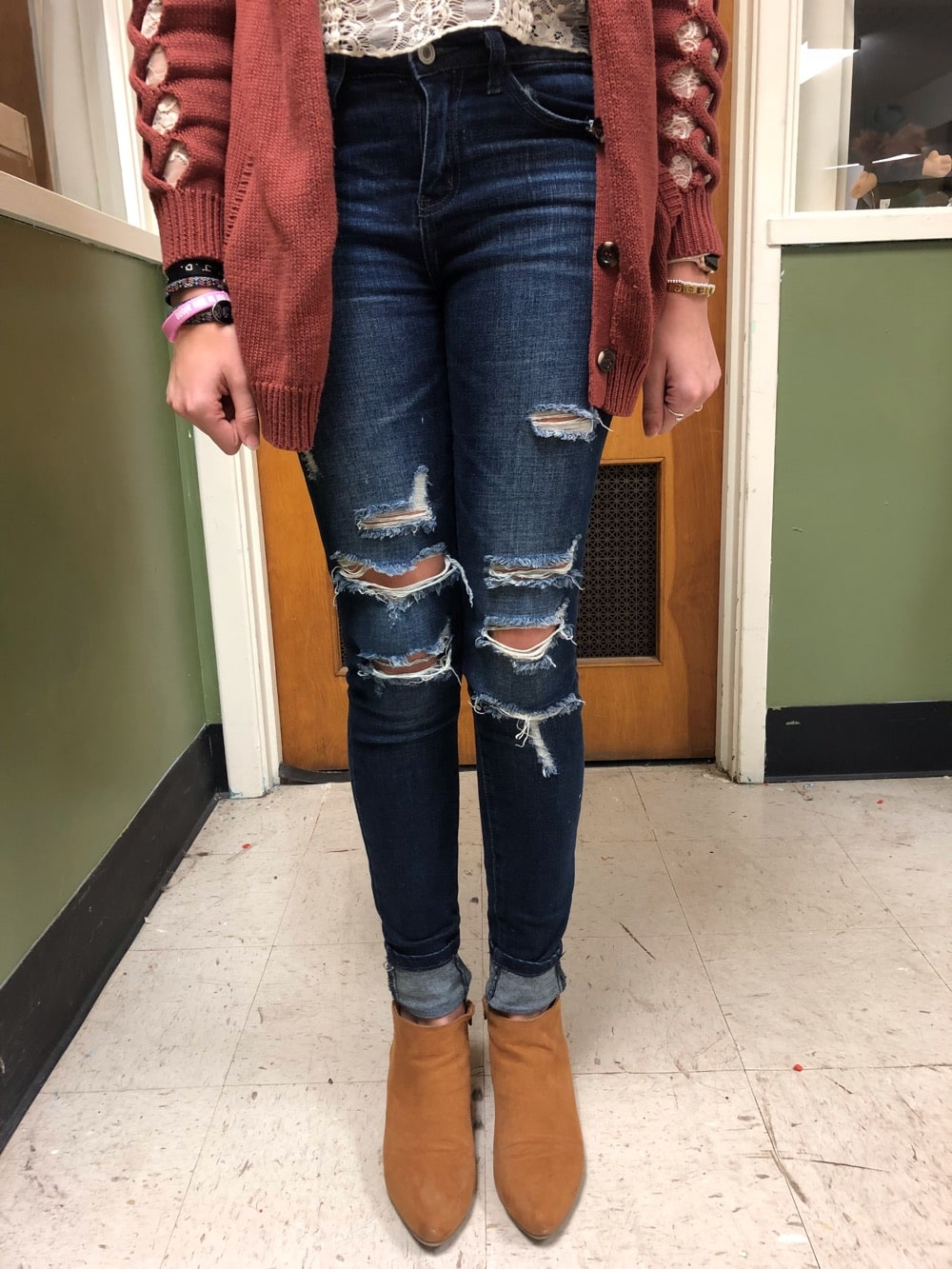 Gentry wears ripped dark blue skinny jeans with pointed toe camel chelsea boots.