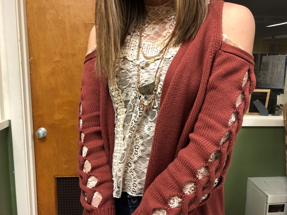 Gentry pairs her cream high neck blouse with a burnt sienna red sweater with open shoulders and cut sleeves.