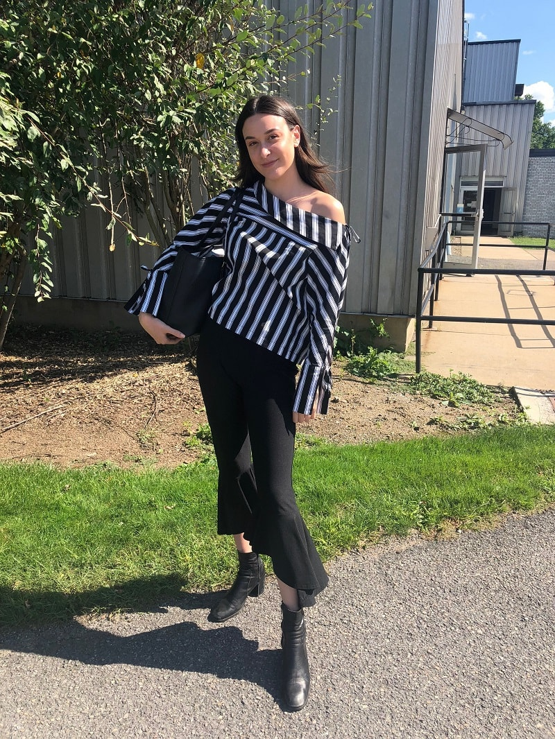 West Virginia University student Georgia wears a striped off-the-shoulder black and white blouse with bell sleeves, black cropped flare trousers, and black chunky heeled boots.