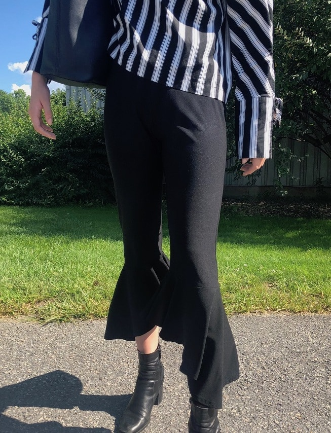 Georgia's pants are black cropped trousers with a ruffled flare.